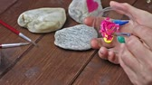 stylish : Womans hand is is smudging color in a glass bowl before painting an abstract on stone