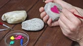 Female hand is painting on a stone heart by brush.
