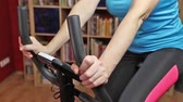 Middle age woman cycling on bike trainer indoors closeup.