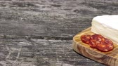 hearty : Footage showing a moving camera focusing on the old wooden desk with hot sausage Chorizo, tomatoes, garlic bulb and a piece of the Petite Brie cheese.