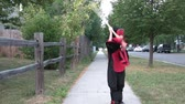 Boy approaches camera swinging a bamboo stick dressed in a black and red ninja costume on a sidewalk in summer.
