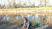 Boy stands on river bank in sun and throws brown leaves into air with mouth open showing excitement.  Vídeos
