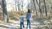 koruyucu : Brother and sister hold hands while they walk through woods in fall down a dirt road at sunset.