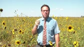 Businessman in red tie eats an apple for healthy snack in a brightly lit sunflower field with blue sky as background.