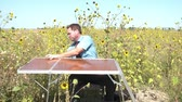 Businessman in sun has office set up in wild sunflower field; puts laptop in case, and then folds up table, grabbing case, and chair to leave.