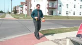 Businessman crosses street in sun, sits down on bench sipping drink, and proceeds to open brown lunch bag to eat meal.