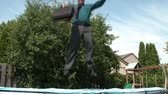 Man in business shirt and tie holds case and jumps up and down, laughing, twisting, and then jumps off into yard, in sunlight.