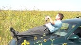 Businessman is laying on the hood of a green car in a sunflower field, and picks up electronic tablet for a moment to use, in bright sunlight.
