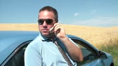 Business person on phone against newer blue car with waving wheat field in background, and bright blue sky. Vídeos