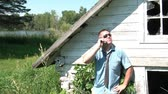 Businessman with necktie undone talks on phone leaning against an old abandoned structure in a rural setting. Vídeos