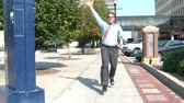 Businessman wearing tie runs towards camera on sunny day failing to wave down his next ride or taxi with frustration, in downtown urban setting.