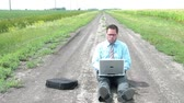 Businessman is sitting on dirt road between two farm fields using laptop computer in sunlight before closing it, and then gazing away into the distance.