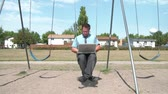 Businessman swinging at playground with laptop computer on legs, typing keys while swing rocks him gently, then stops and walks by, in sunlight.