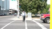 A businessman dressed formally walks in crosswalk across street, and eventually passes frame during afternoon downtown.