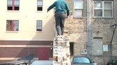 Businessman walks narrow brick ledge high in the air in downtown setting while trying not to fall in the meantime. Vídeos