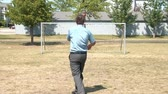 Businessman kicks soccer ball over goal in sunshine, and then throws fit after missing mark. Vídeos