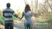 wispy : Couple walks in the fall season together, holding hands and talking down a wooded dirt road near river bank in afternoon.