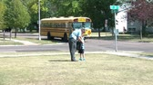 Dad in business attire meets kids in front yard after bus drops them off after school. Vídeos