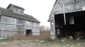 falling down : Pan of farm in ruins with dilapidated wood siding and paint, starting from farmhouse, and ending at old barn hayloft doors. Stock Footage