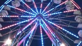 fairgrounds : Slow pan up of colorful ferris wheel at night with colors flashing on metal framing, and then a pan down at end.