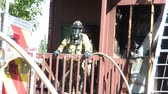gutted : Fireman with black respirator mask stands on apartment balcony in sunlight awaiting item with fire contained in background.