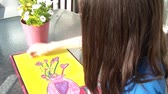 wazon : Girl colors original drawing with yellow crayon in sunlight, and then turns around and asks for thoughts.  Wideo