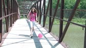 élvezve : Girl kicks pink ball over bridge while running after it in sunlight, reaching cement entrance to park at end.