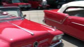 Pan of classic red cars in sunshine with maximum reflection from paint and chrome.