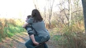 namorado : Man carries woman on back playfully as they walk past in wooded area during romantic autumn day, mans spins toward end.