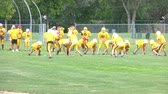 Yellow junior varsity high school football team practices in morning sunlight. Stock Footage
