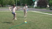 sonhar : Kids running through unique sprinkler in yard while playing with bubbles in the air during bright summer afternoon. Stock Footage