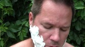 kazınmış : Close up clip of man putting shaving cream on his face in exterior lighting, and with lush green leaves as a natural background.