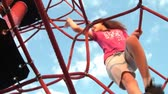 Girl climbs ropes obstacle to the top during sunset, shot from below. Vídeos