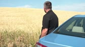 Man in black leaning against car near beautiful wheat field with brilliant colors bisecting the horizon.