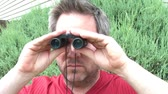 Man in sunlight looks through binoculars after looking at camera, looks around and then takes away from face.