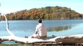 Man in sunlight sits on white driftwood tree over lake and stares at the scenic views of the fall foliage during autumn season on a Minnesota lake.