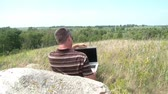 Guy sits atop a hill overlooking valley, and leisurely opens up laptop computer with expansive view in background.