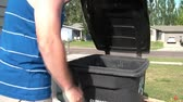 Clip of man placing garbage bag into black plastic garbage can in natural sunlight.