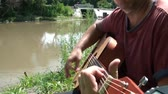 versão : Man strums and picks his acoustic guitar on river bank in summer sunshine.