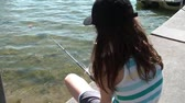 incandescente : Youthful girl fishes off of dock at sunny scenic lake in Minnesota during sunny morning. Stock Footage
