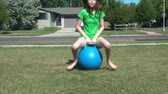 Young girl hops by sitting and bouncing on blue ball in yard towards camera, and then passes, on sunny afternoon.
