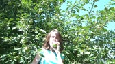 crescido : Girl picks a green apple from tree and turns to camera to eat fruit in summer sunshine.