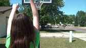 Young girl shoots baskets with her green basketball in driveway, outside in the sunshine.