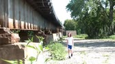 wispy : Young girl in sun walks next to rusty railroad bridge approaching camera, in summer attire, and then passes by frame.  Stock Footage