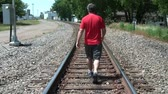 condutor : Man in red shirt walking away from camera down railroad tracks in summer.
