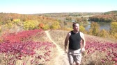 Man jogs up trail on steep hill in autumn with scenic colors in trees, lakes, and blue skies in background. Vídeos