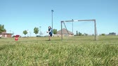 Girl stands in goal in sunlight while foot kicks soccer ball towards her, saving one, the other bouncing off cross bar.