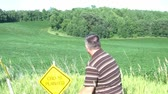 caqui : Man pounds down yellow crops planted sign down into ground while field below blows beautifully in the wind. Vídeos