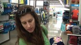 определенный : Attractive young woman shopping for kids clothes and continues to browse towards clips end. Стоковые видеозаписи