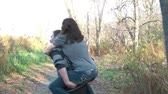 Man carries woman on back playfully as they walk past in wooded area during romantic autumn day, mans spins toward end.